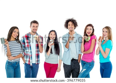 Studio shot of nice young multicultural friends. Beautiful people with cups of coffee and donuts looking at camera and smiling. Isolated background - stock photo