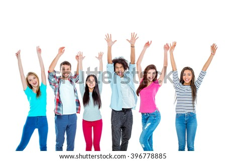 Studio shot of nice young multicultural friends. Beautiful people with hands up looking at camera and cheerfully smiling. Isolated background