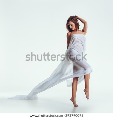 Studio shot of nude brunette posing with a sheer fabric on her body. Full length portrait of caucasian female model naked, wrapped in a transparent cloth posing sensually on white background.  - stock photo