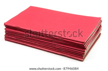 Studio shot of old red exercise books stack on white background - stock photo