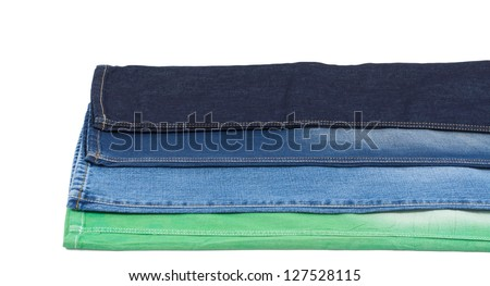 Studio shot of one leg from four different pairs of jeans overlaid to display the different colours of denim fabric from green through blue to navy blue isolated on white - stock photo