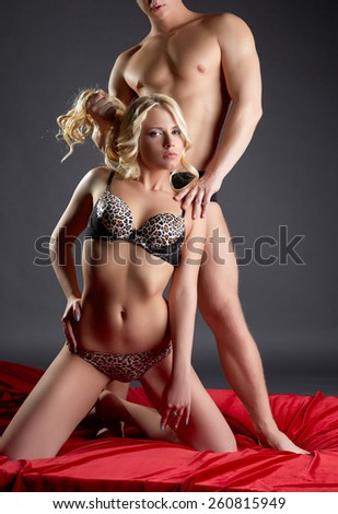 Studio shot of passionate couple posing in bed - stock photo