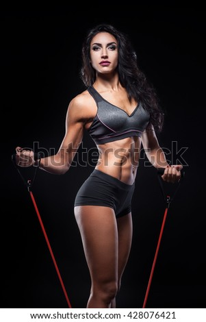 studio shot of perfect body of bodybuilder female with expander; fitness woman with sexy muscular torso on black background and with gym equipment;