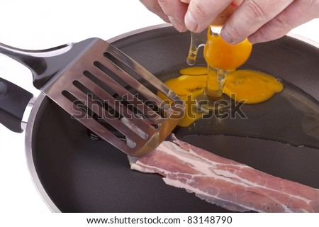 studio-shot of preparing breakfast in a frying pan with bacon and fried eggs, isolated on white. - stock photo
