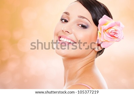 studio shot of pretty smiley model with rose in hair - stock photo