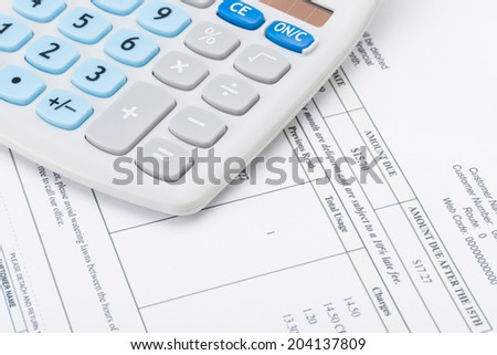 Studio shot of receipt next to calculator - stock photo