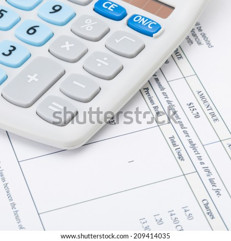 Studio shot of receipt next to calculator - 1 to 1 ratio - stock photo