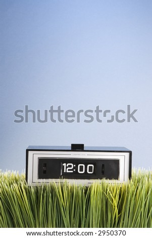 Studio shot of retro alarm clock placed in grass. - stock photo