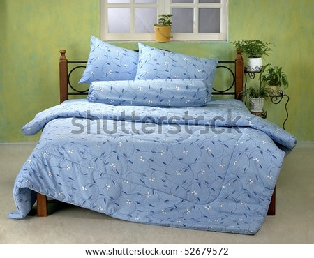 Studio shot of room interior with queen size bed and plants decorations. - stock photo