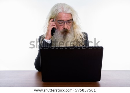 Studio shot of senior bearded businessman talking on mobile phone while using laptop on wooden table