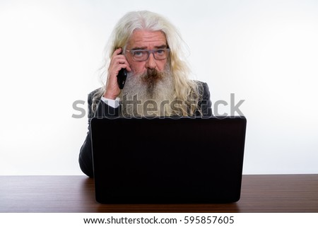 Studio shot of senior bearded businessman talking on mobile phone with laptop on wooden table