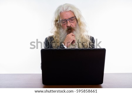 Studio shot of senior bearded businessman thinking while wearing eyeglasses and using laptop on wooden table