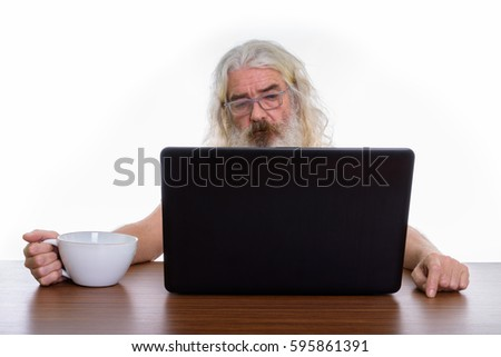 Studio shot of senior bearded man holding coffee cup while using laptop on wooden table