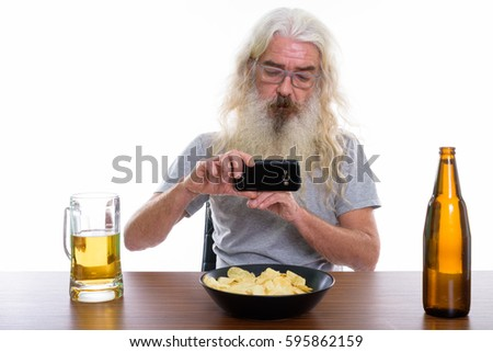 Studio shot of senior bearded man taking picture with mobile phone of beer and bowl of potato chips on wooden table