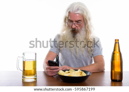 Studio shot of senior bearded man using mobile phone with beer and bowl of potato chips on wooden table