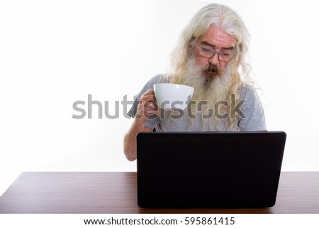 Studio shot of senior bearded man wearing eyeglasses and holding coffee cup while using laptop on wooden table