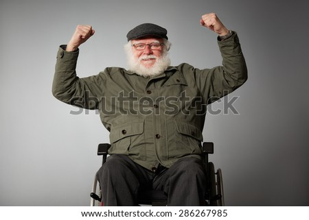 Studio shot of senior man sitting in wheel chair cheering with his fist clenched against grey background - stock photo