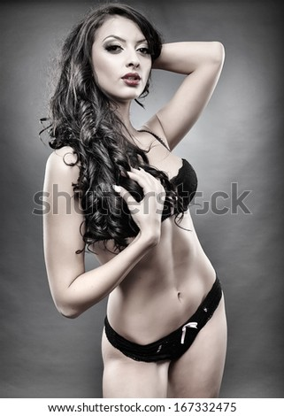 Studio shot of sexy brunette in black lingerie - stock photo