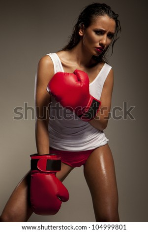 Studio shot of sexy female fighter with red boxing gloves - stock photo