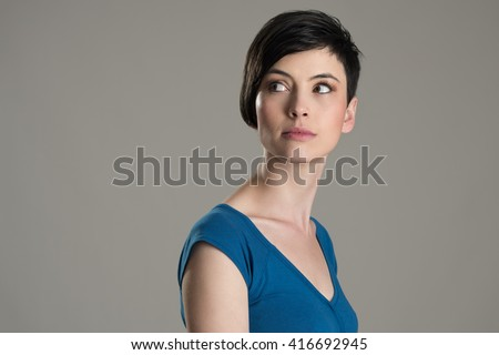 Studio shot of short hair beauty model looking back over the shoulder with copyspace over gray background - stock photo