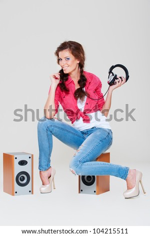 studio shot of smiley woman sitting on speakers over grey background - stock photo