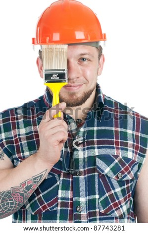 Studio shot of smiling foreman in work shirt and hard-hat holding a paint brush in front of his face - stock photo