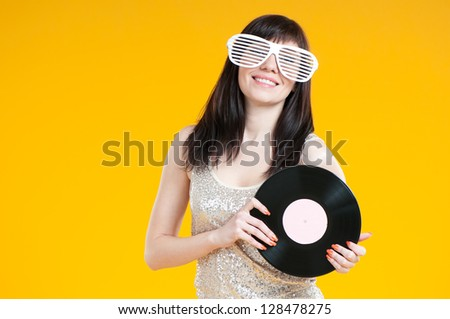 Studio shot of smiling girl in funny eyeglasses with a vinyl disc - stock photo