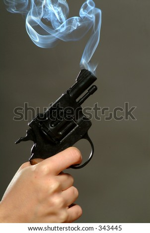 Studio shot of smoking pistol - stock photo