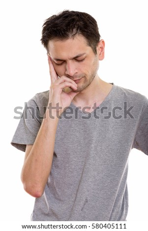 Studio shot of stressed young man having headache with eyes closed