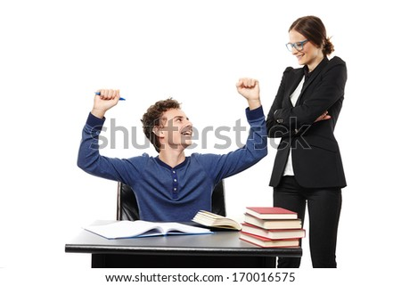 Studio shot of student sitting at his desk looking happily at his teacher and throwing hands in the air, isolated over white background - stock photo
