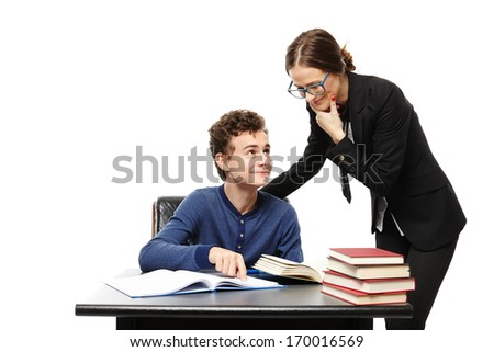 Studio shot of teacher standing next to student's desk with hand on chin and the student pointing the teacher something in the book, isolated over white background - stock photo