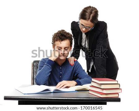 Studio shot of teacher standing next to student's desk with hand on his shoulder looking into his homework, isolated over white background - stock photo