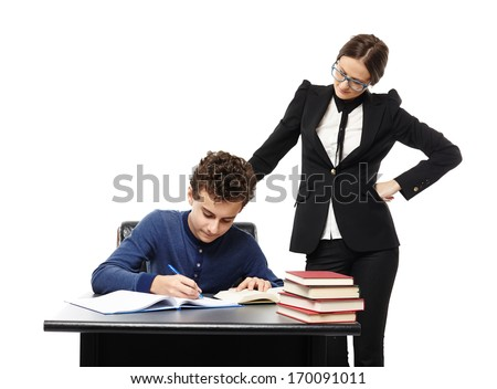 Studio shot of teacher standing next to student's desk with hand on waist, supervising him, isolated over white background - stock photo