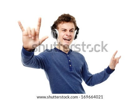 Studio shot of teenager dancing, enjoying listening to music at headphones and making the rock and roll sign, isolated over white background - stock photo