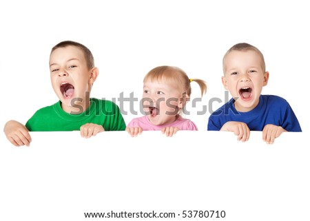 studio shot of three child behind white board - stock photo