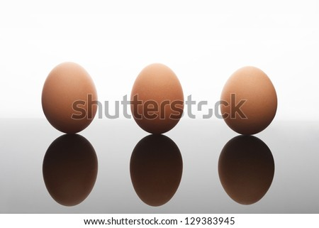 studio shot of three eggs standing strait on reflective surface - stock photo