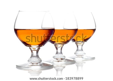 Studio shot of three glasses of cognac isolated on white - stock photo