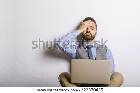 Studio shot of tired hipster businessman working on laptop - stock photo