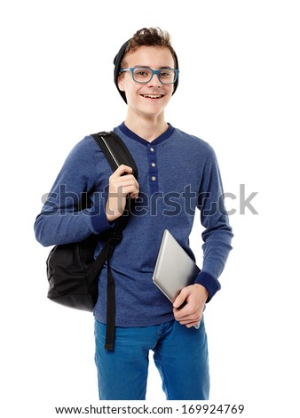 Studio shot of trendy cheerful teenager with backpack, wearing cap and glasses and holding a tablet - stock photo
