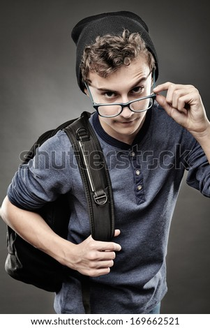 Studio shot of trendy handsome teenager with backpack looking above the glasses