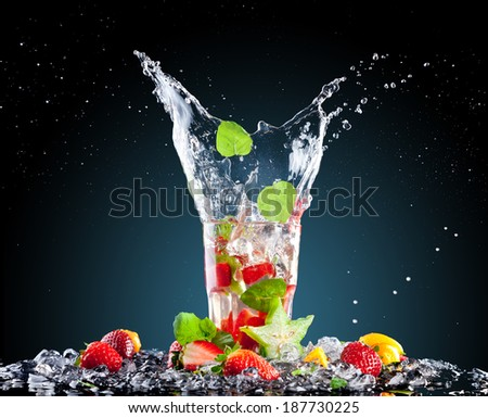 Studio shot of tropical cocktail with ice cubes and splash. - stock photo