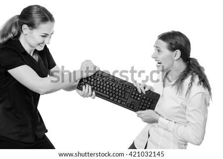 studio shot of two business models having a disagreement whilst pulling at a keyboard.  isolated on white