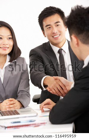 Studio Shot Of Two Chinese Businessmen Shaking Hands During Meeting - stock photo