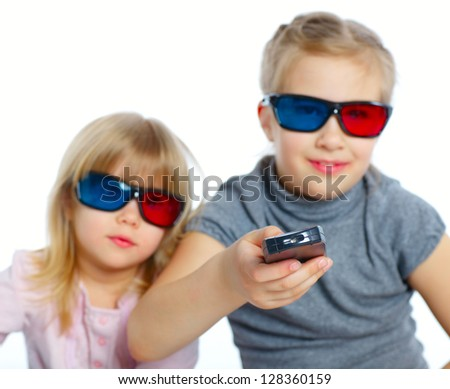 Studio shot of two girls in 3d glasses with control panel watching TV. Focus on the control panel. Isolated white background - stock photo