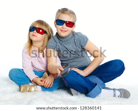 Studio shot of two girls in 3d glasses with control panel watching TV. Isolated white background - stock photo