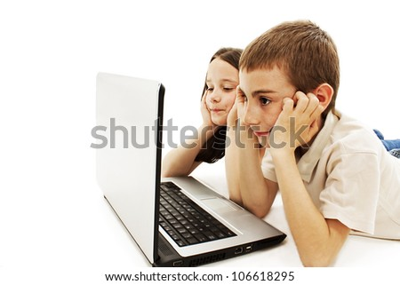 Studio shot of two kids with laptop. Isolated on white background. - stock photo