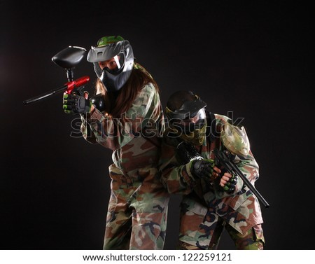 Studio shot of two paintball players on black background
