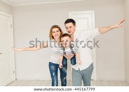 Studio shot of two parents playing with their boy child. They made a plane with their hands and have fun with their kid. They wear white t-shirt and jeans.  - stock photo