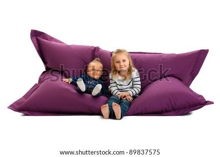 studio shot of two sister sitting on beanbag - stock photo