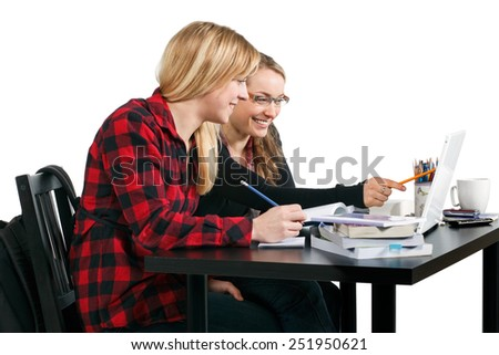 Studio shot of two students working at a desk isolated on white.